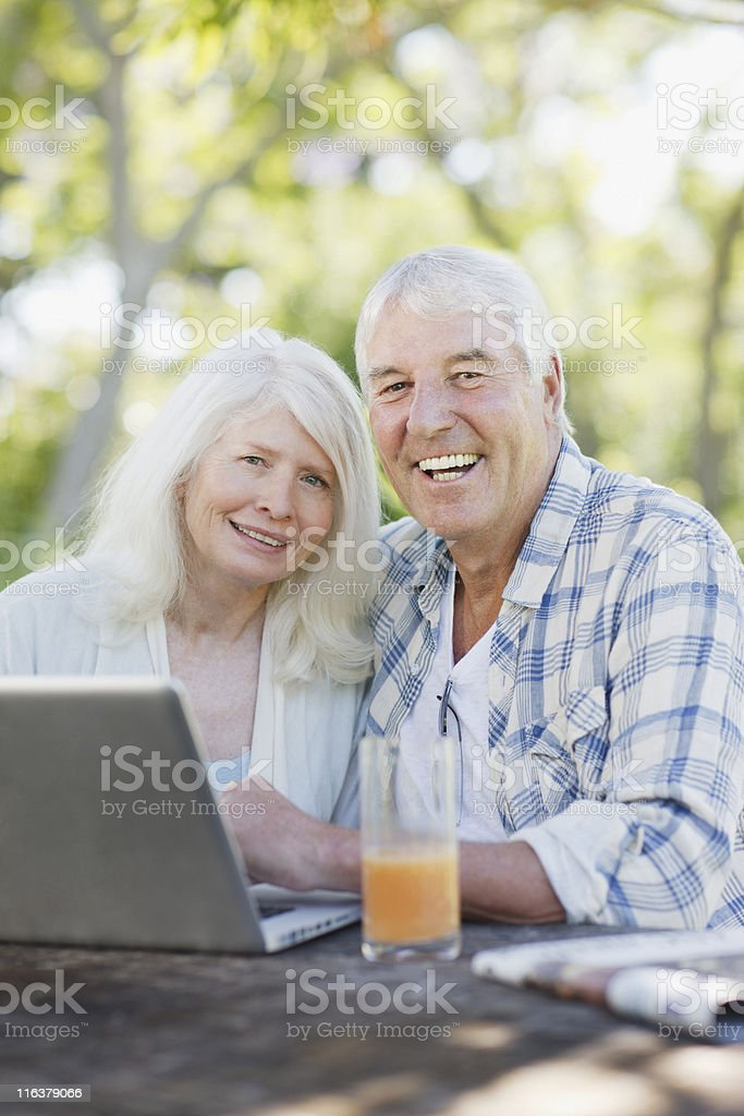 Senior couple using laptop at patio table royalty-free stock photo
