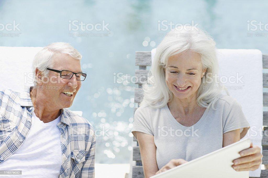 Senior couple using laptop at poolside royalty-free stock photo