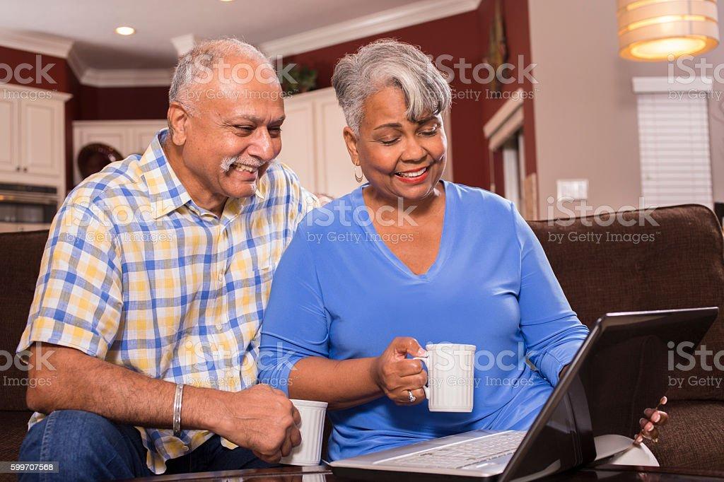 Senior couple using laptop computer at home. stock photo