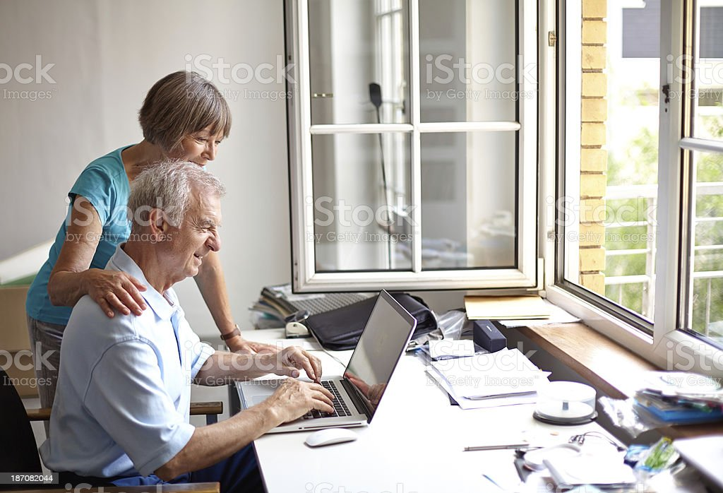 senior couple using laptop in home office royalty-free stock photo