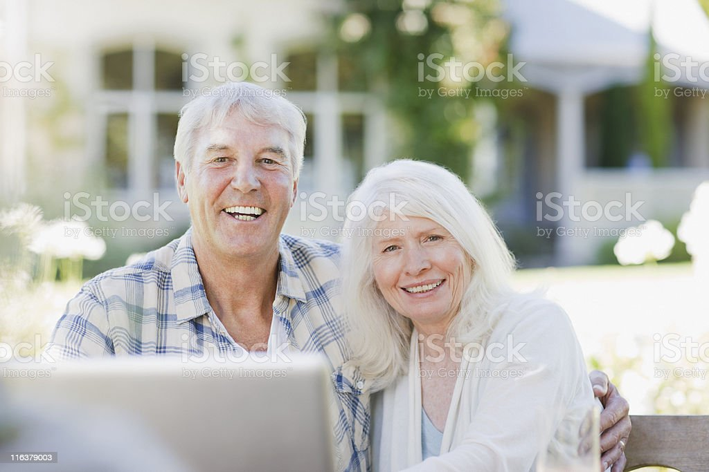 Senior couple using laptop on patio royalty-free stock photo