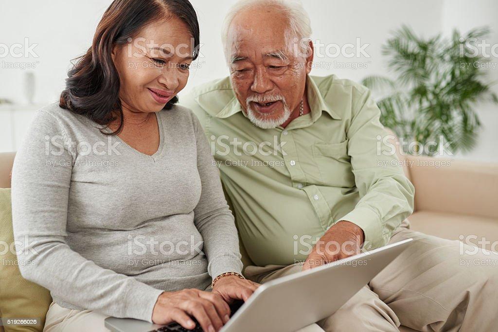 Senior couple using laptop stock photo