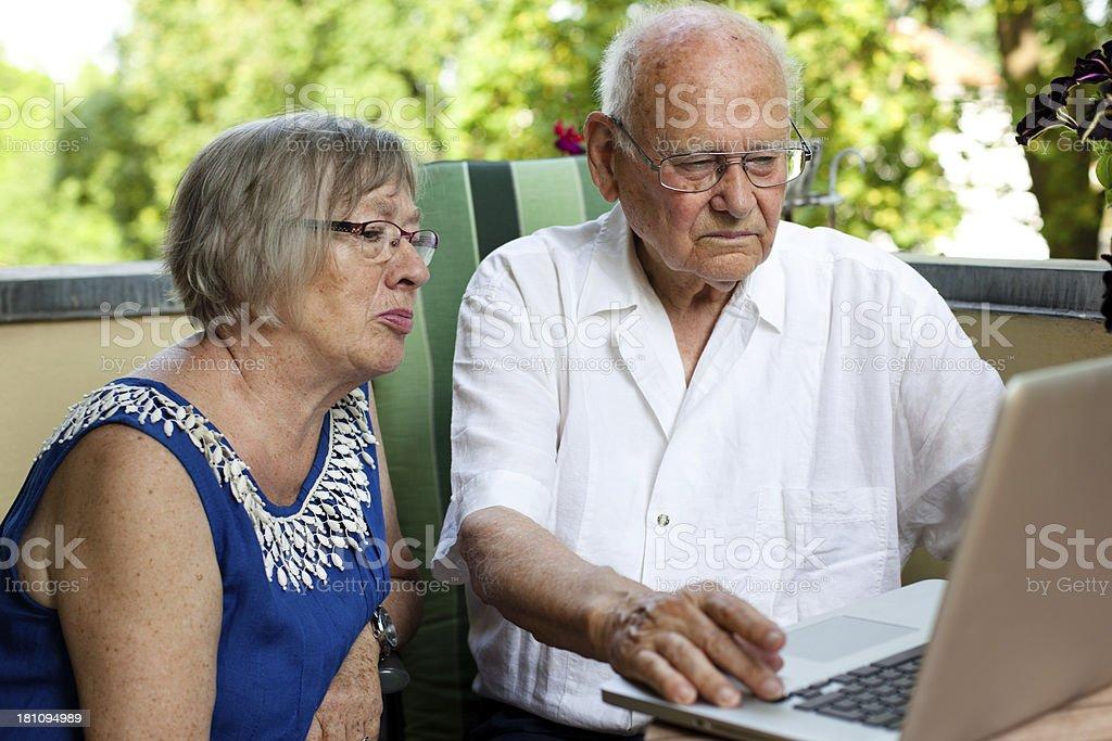 senior couple using laptop, sit on the balcony royalty-free stock photo