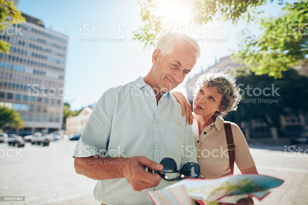 Senior couple using road map in a foreign city stock photo