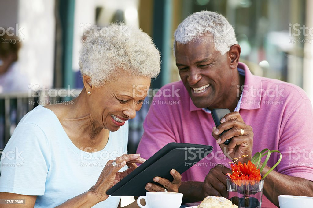 Senior Couple Using Tablet Computer At Outdoor Cafe royalty-free stock photo