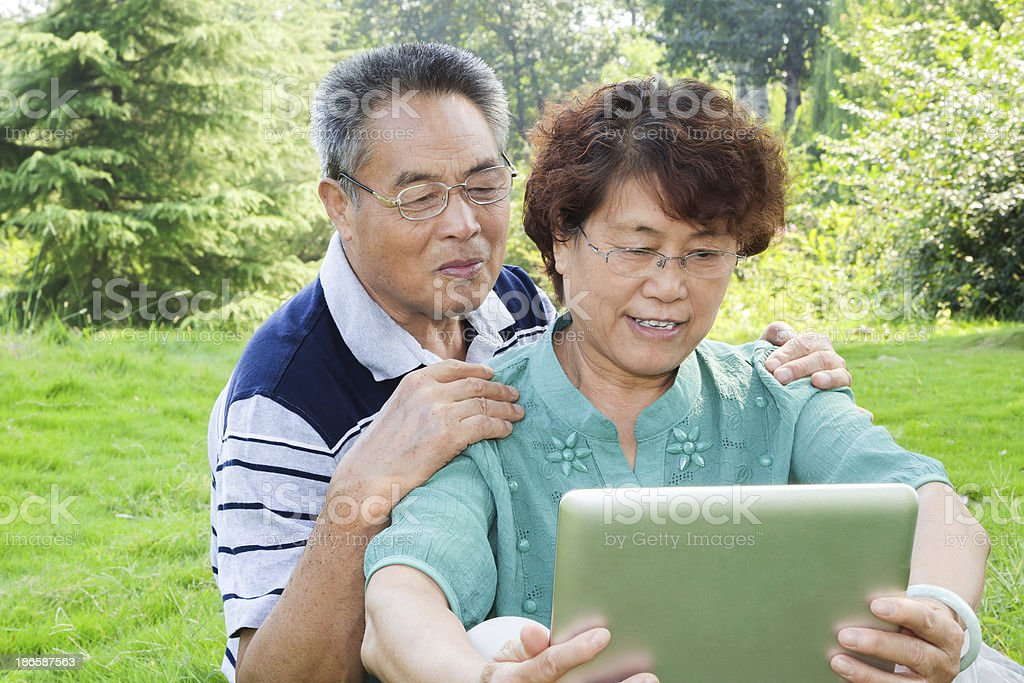 Senior Couple using Tablet Computer in Park royalty-free stock photo