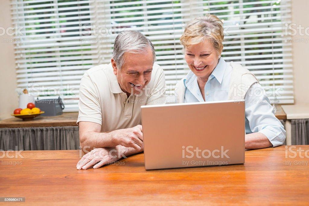 Senior couple using the laptop together stock photo