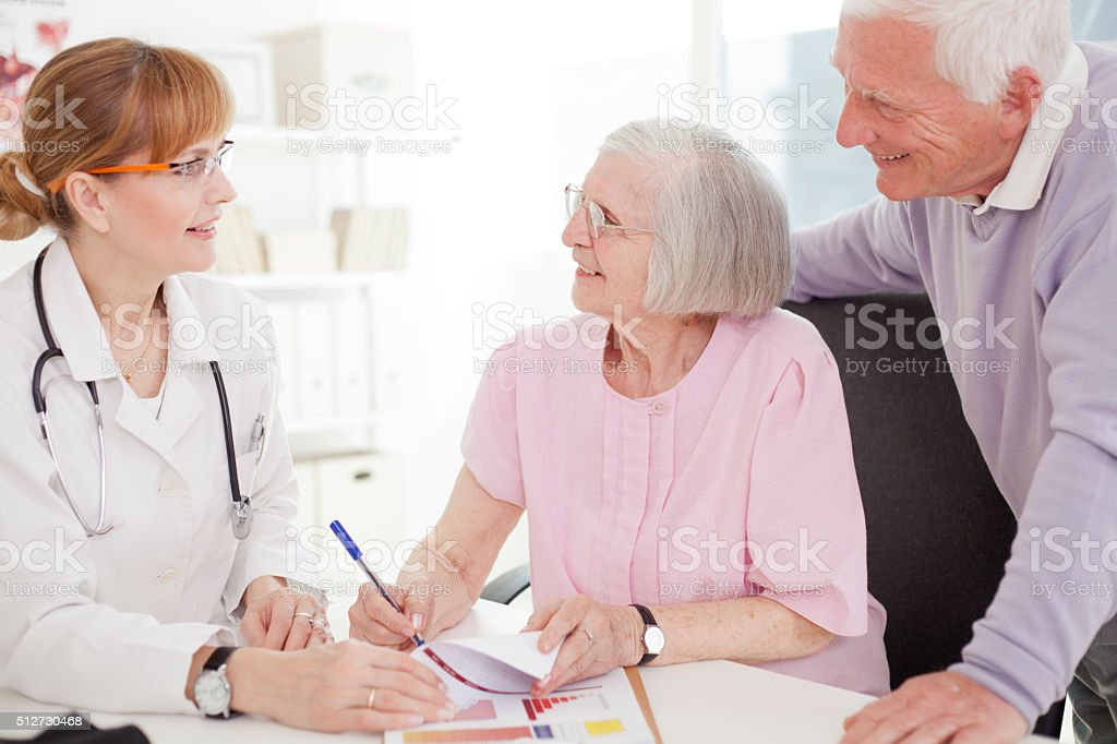 Senior couple visiting doctor. stock photo