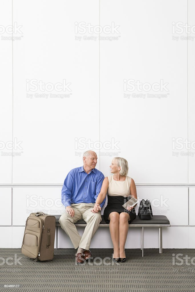 A senior couple waiting on a bench stock photo