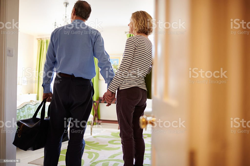 Senior couple walk in to hotel room holding hands, stock photo