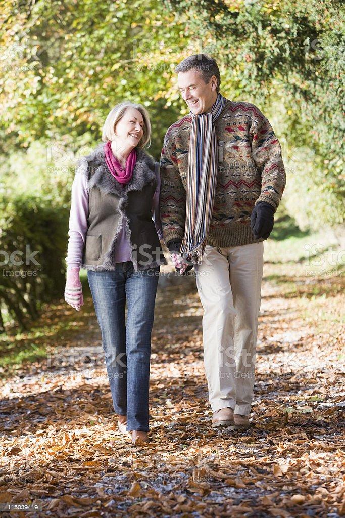 Senior couple walking along autumn path royalty-free stock photo