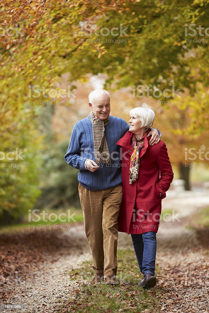 Senior Couple Walking Along Autumn Path stock photo