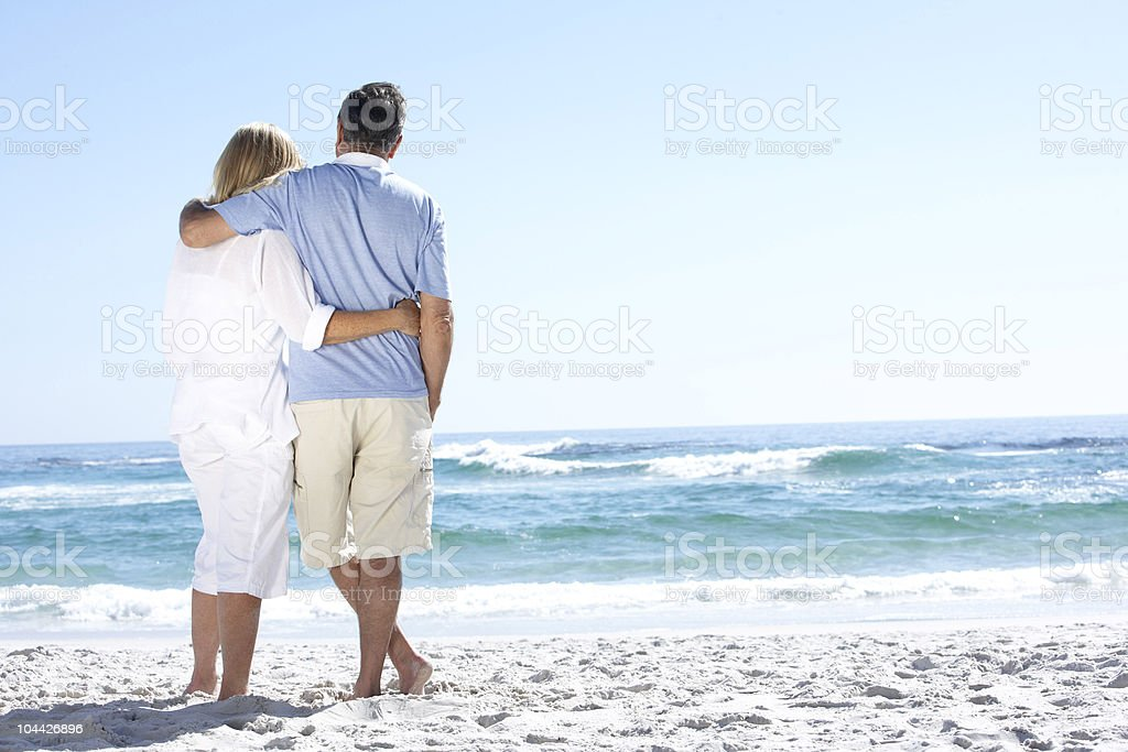 Senior Couple Walking Along Beach Looking Out To Sea royalty-free stock photo