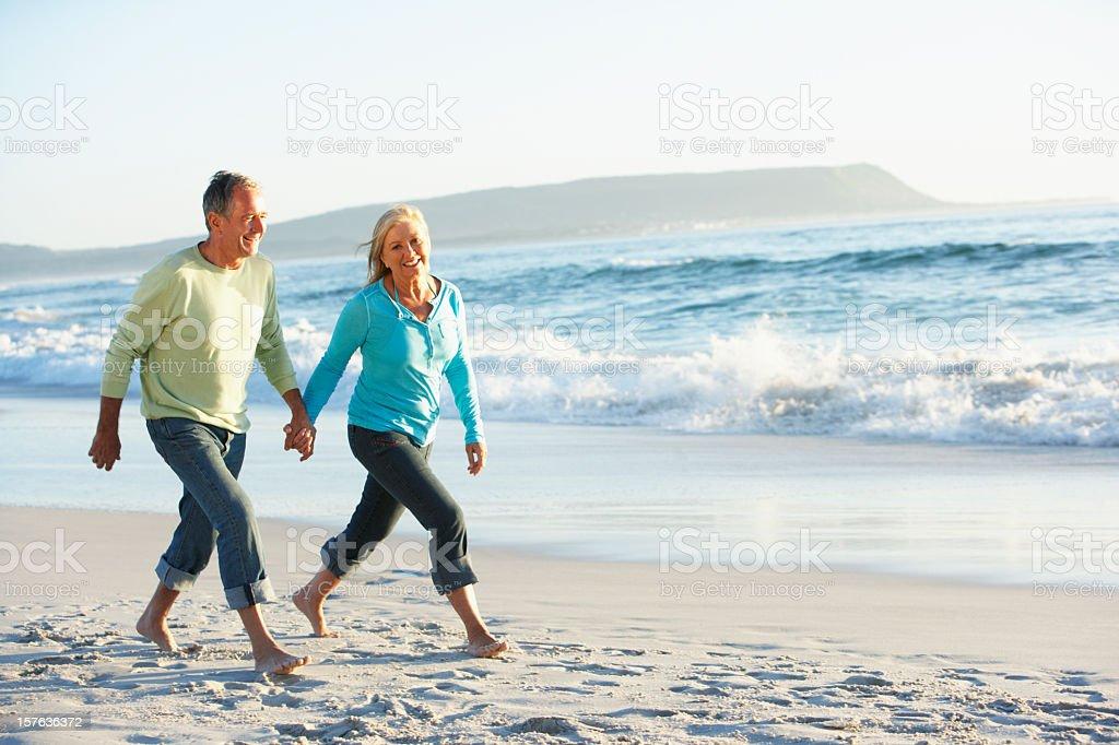 Senior Couple Walking Along Beach royalty-free stock photo