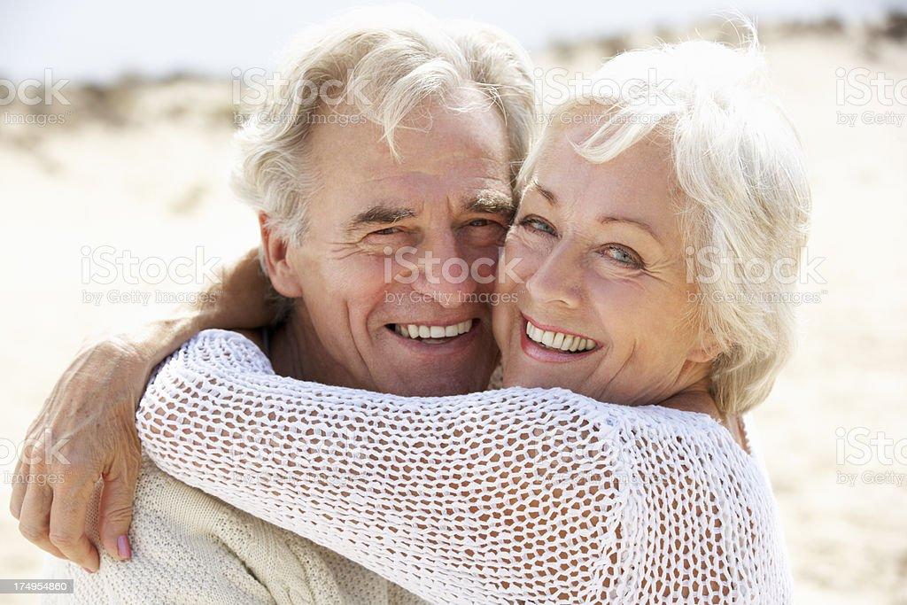 Senior Couple Walking Along Beach Together royalty-free stock photo