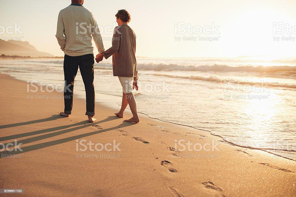 Senior couple walking along the sea shore stock photo