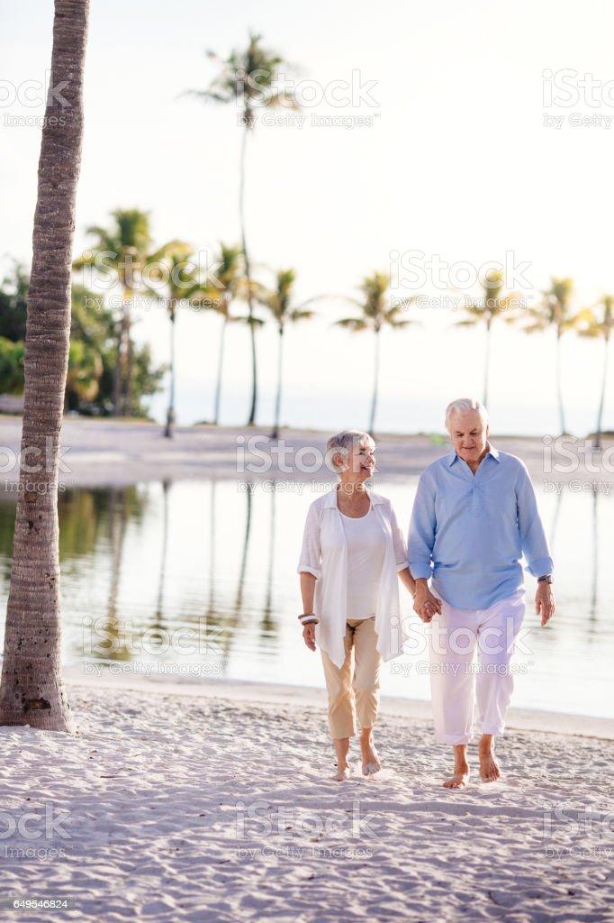 Senior couple walking at the beach stock photo