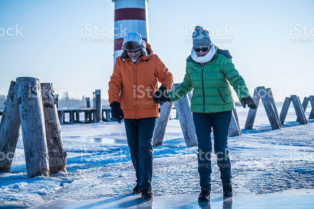 senior couple walking cautios on frozen lake neusiedl stock photo