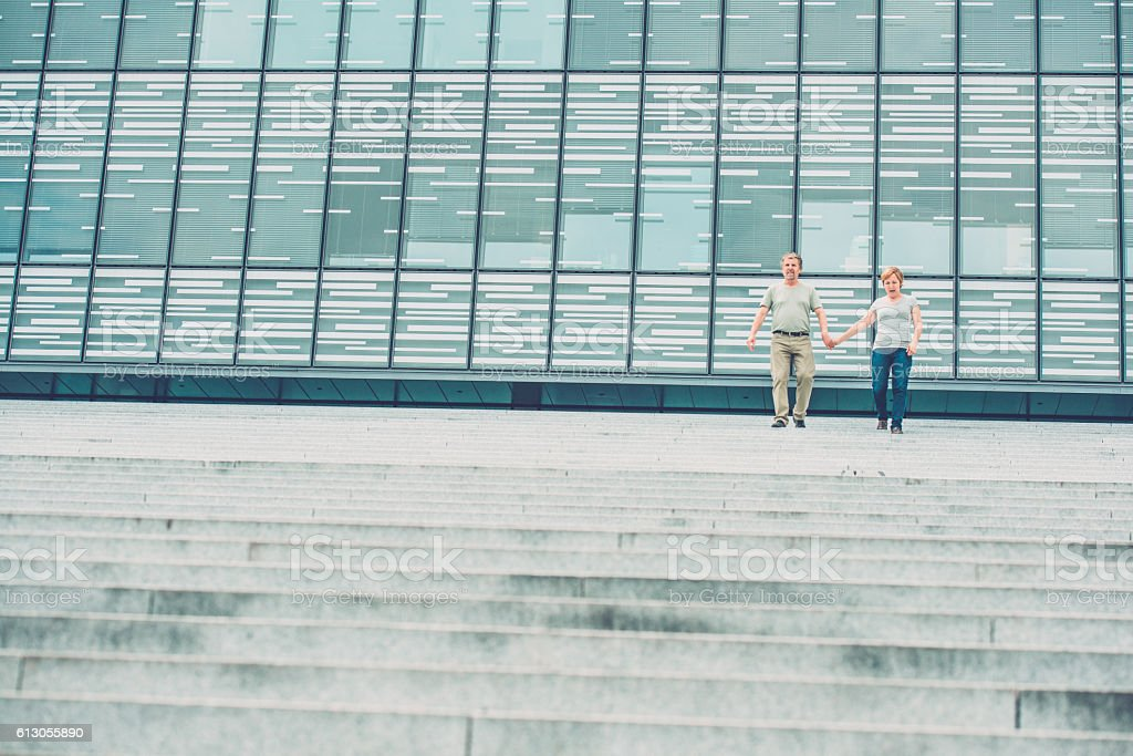 Senior couple walking down stairs of business building stock photo