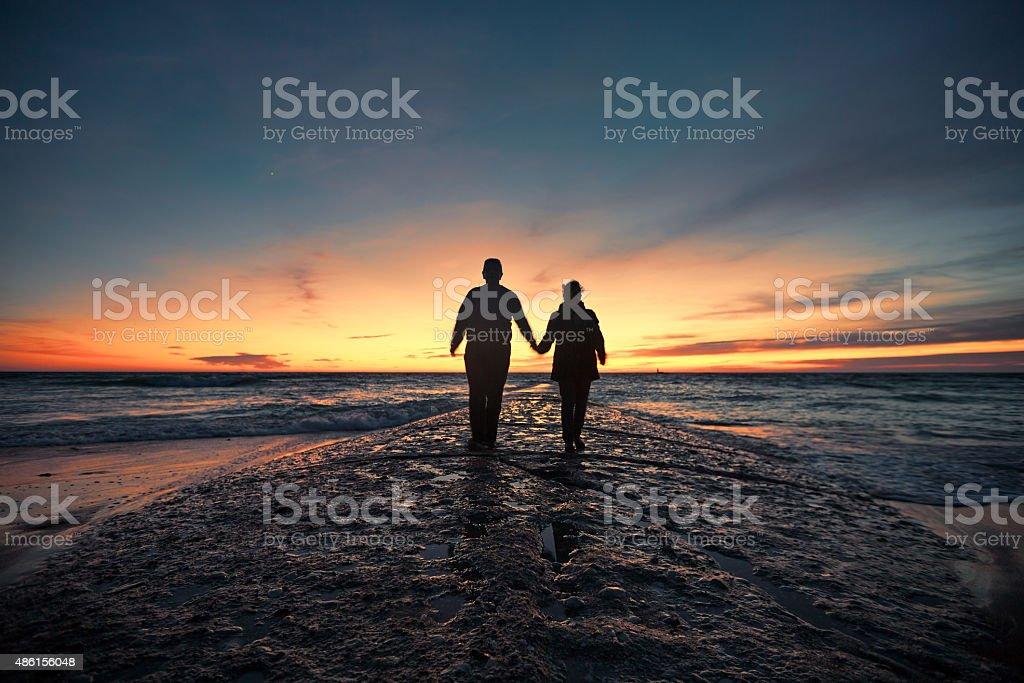 Senior couple walking from seashore at sunset stock photo