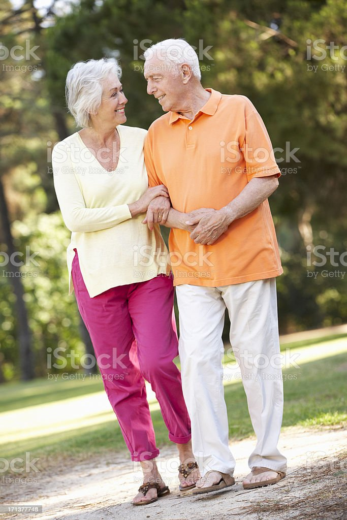 Senior Couple Walking In Park Together stock photo