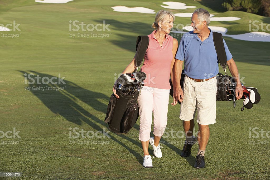 Senior couple walking on golf course with bags stock photo