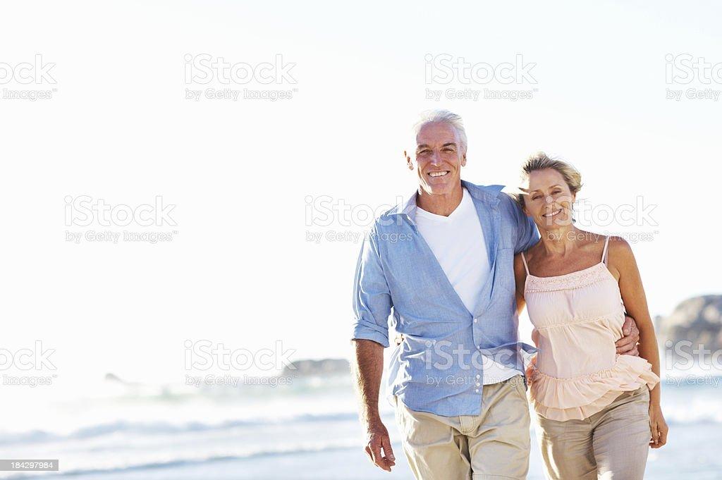 Senior couple walking on the beach royalty-free stock photo