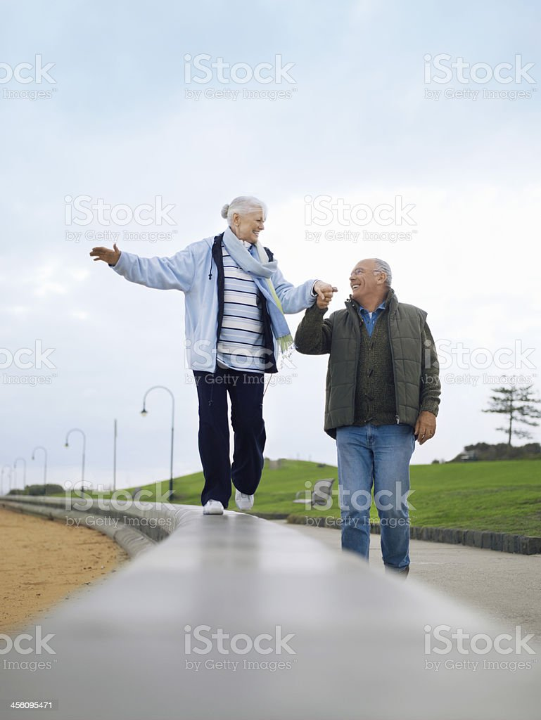 Senior Couple Walking On Wall Holding Hands stock photo