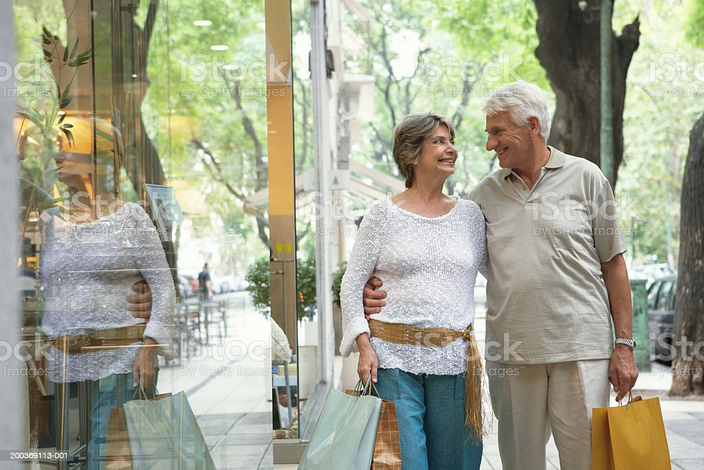 Senior couple walking past shop carrying bags, smiling stock photo