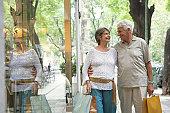 Senior couple walking past shop carrying bags, smiling