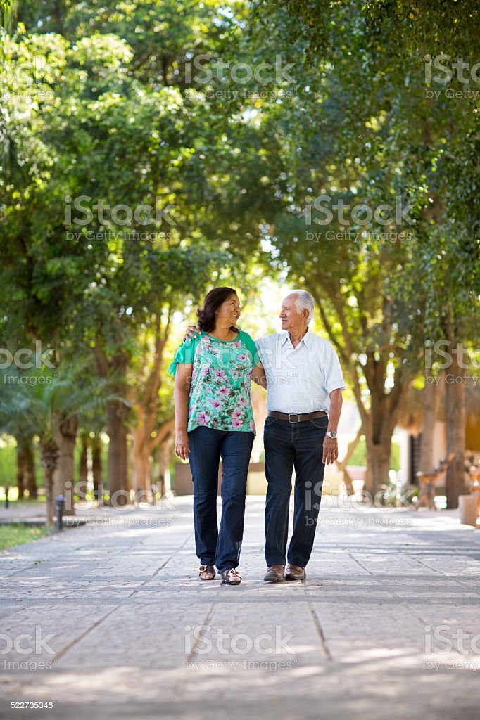 Senior couple walking side by side in park stock photo