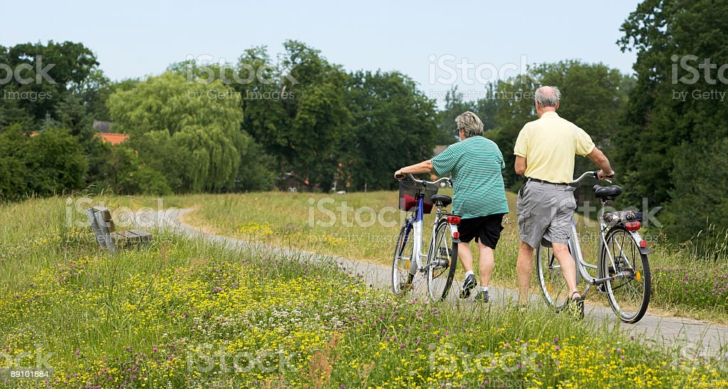 Senior couple walking with bicycles in summer on dyke stock photo