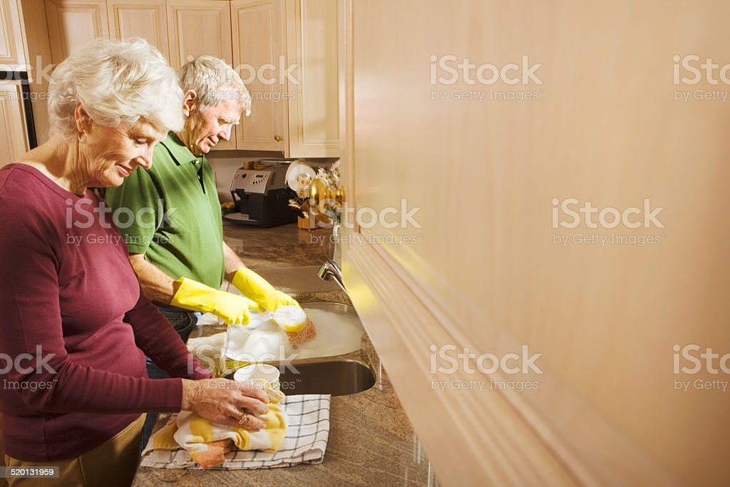 Senior Couple washing dishes in kitchen sink stock photo