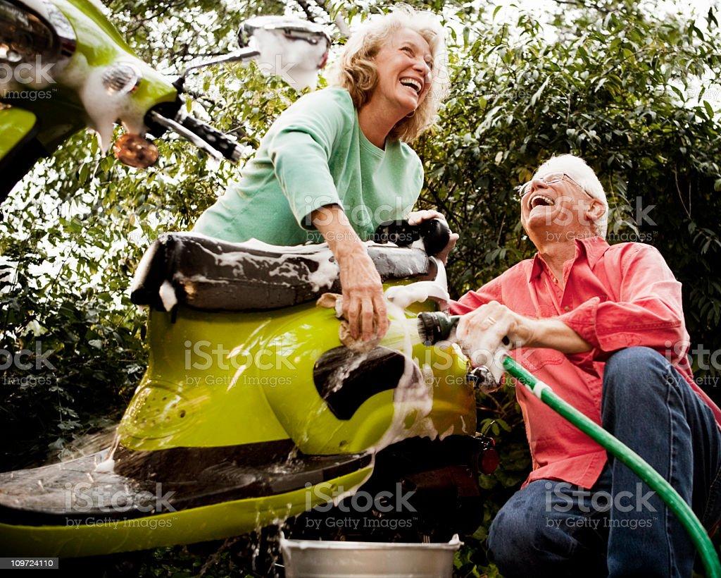 Senior Couple Washing Green Scooter stock photo
