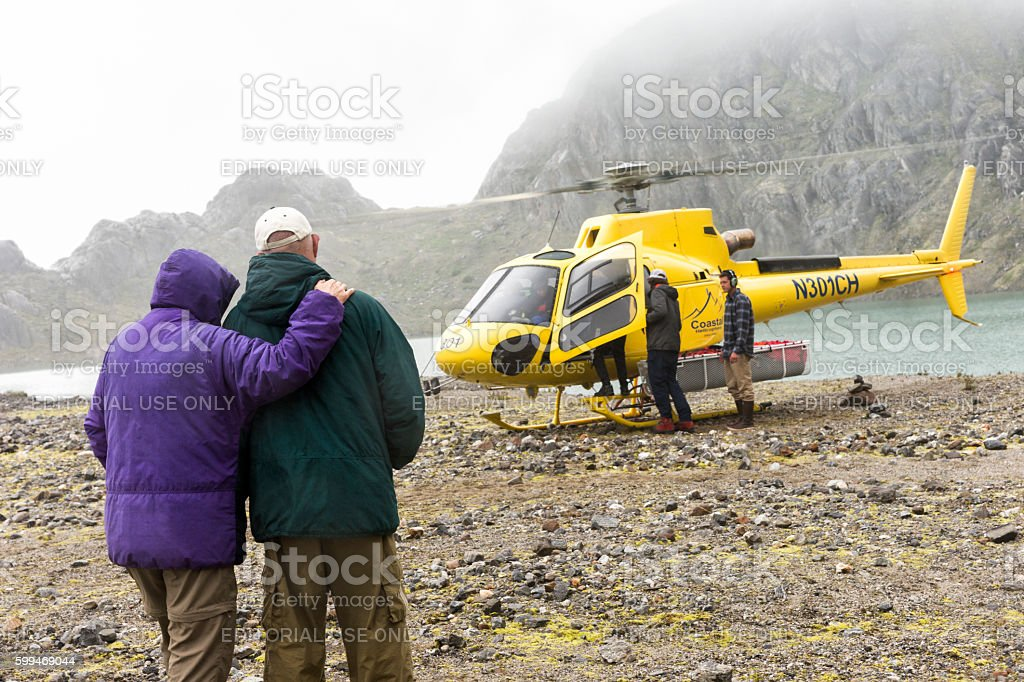 Senior couple watch helicopter landing on glacier stock photo