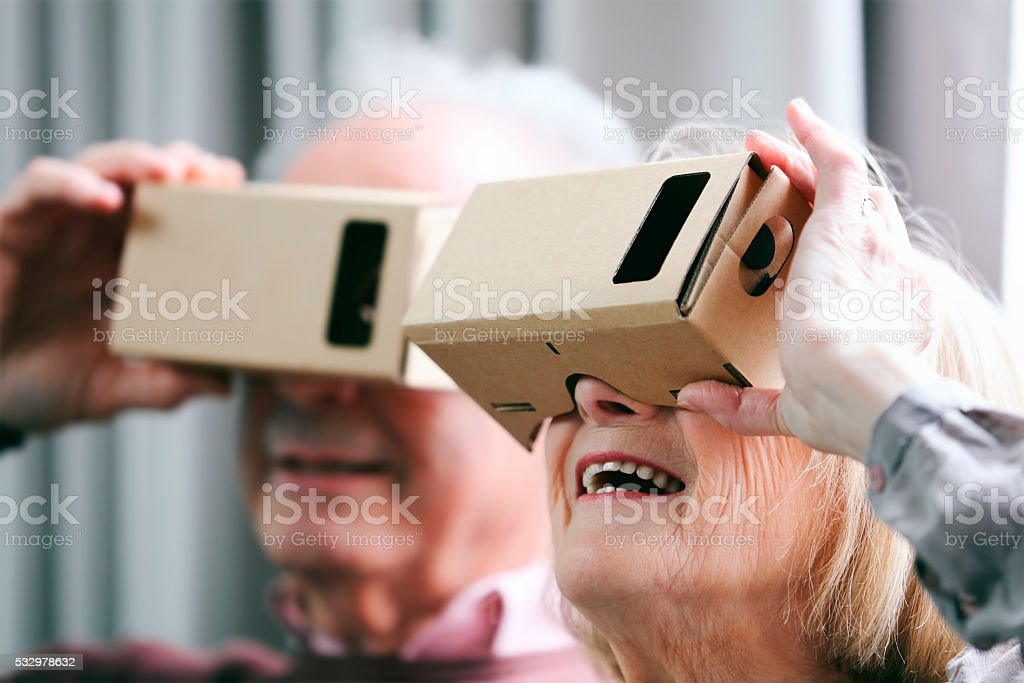 Senior couple watching a film with virtual reality device simulator stock photo