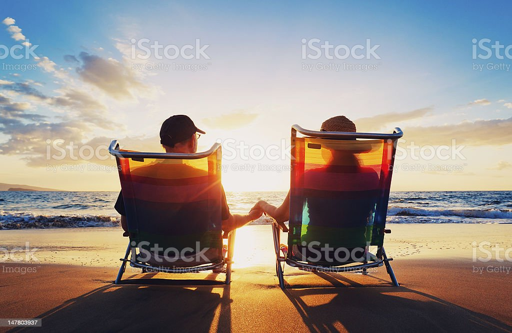 senior couple watching the sunset stock photo