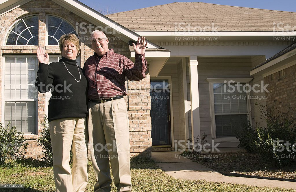 Senior Couple waving in front of house stock photo