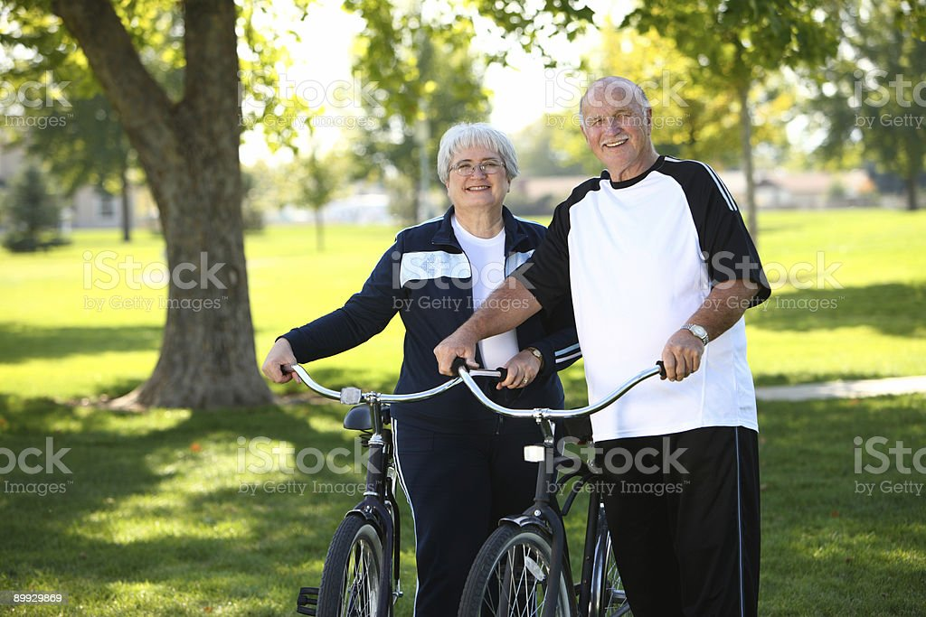 Senior couple with bicycles at park royalty-free stock photo