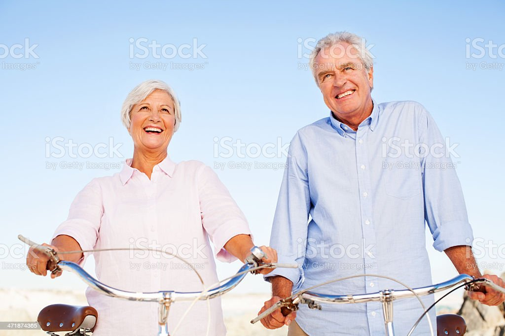 Senior Couple With Bicycles Looking Away Against Clear Blue Sky royalty-free stock photo