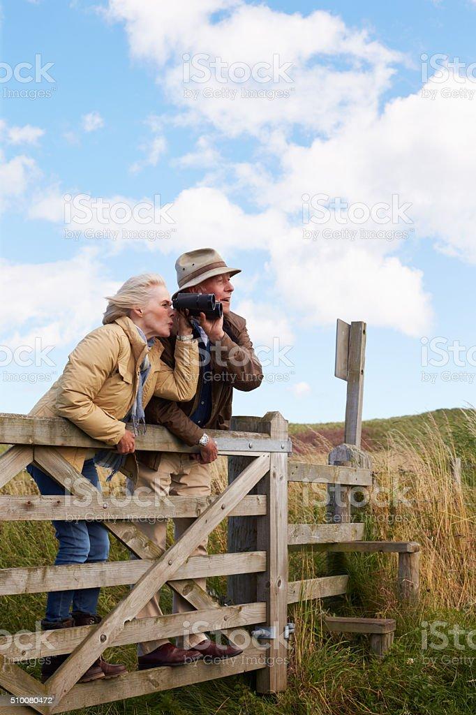 Senior Couple With Binoculars Walking In Countryside stock photo