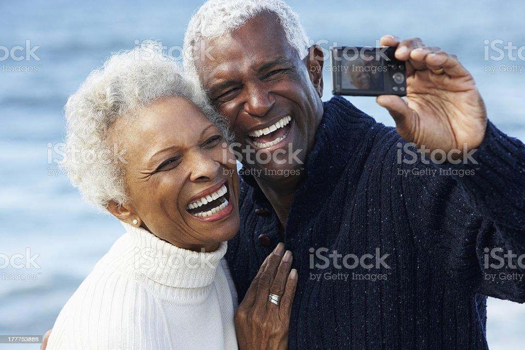 Senior Couple With Camera On Beach stock photo