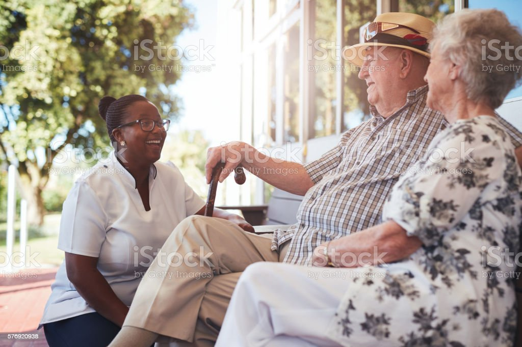 Senior couple with caregiver sitting outside stock photo