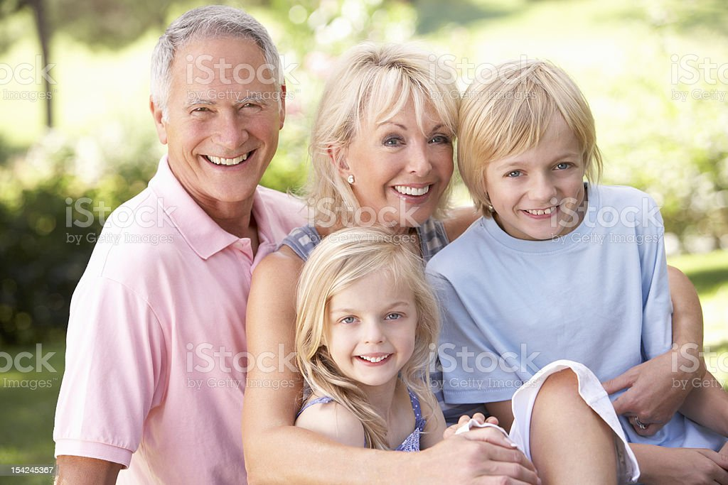 Senior couple with children sitting in park royalty-free stock photo