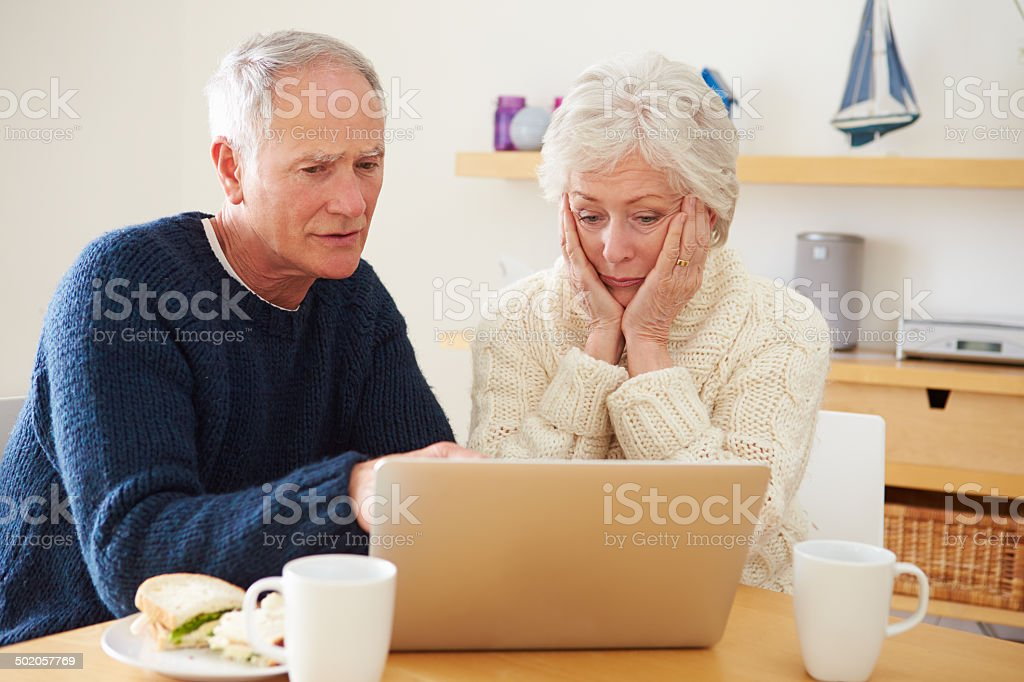 Senior Couple With Financial Problems Looking At Laptop stock photo