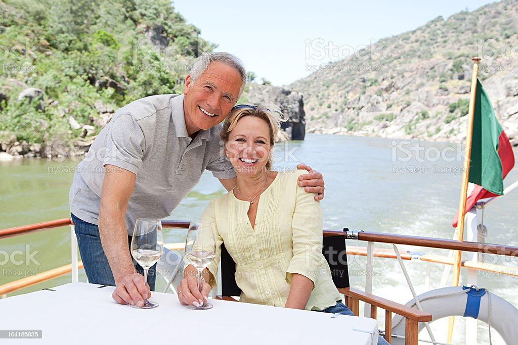 Senior couple with glasses of wine on a boat holiday royalty-free stock photo