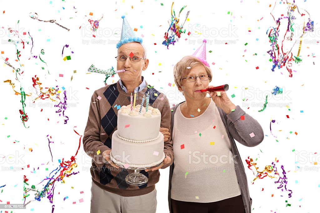 Senior couple with horns and party hats celebrating birthday stock photo