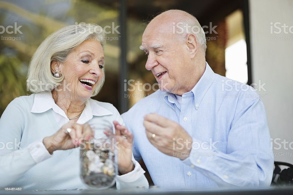 Senior Couple With Jar Of Coins royalty-free stock photo