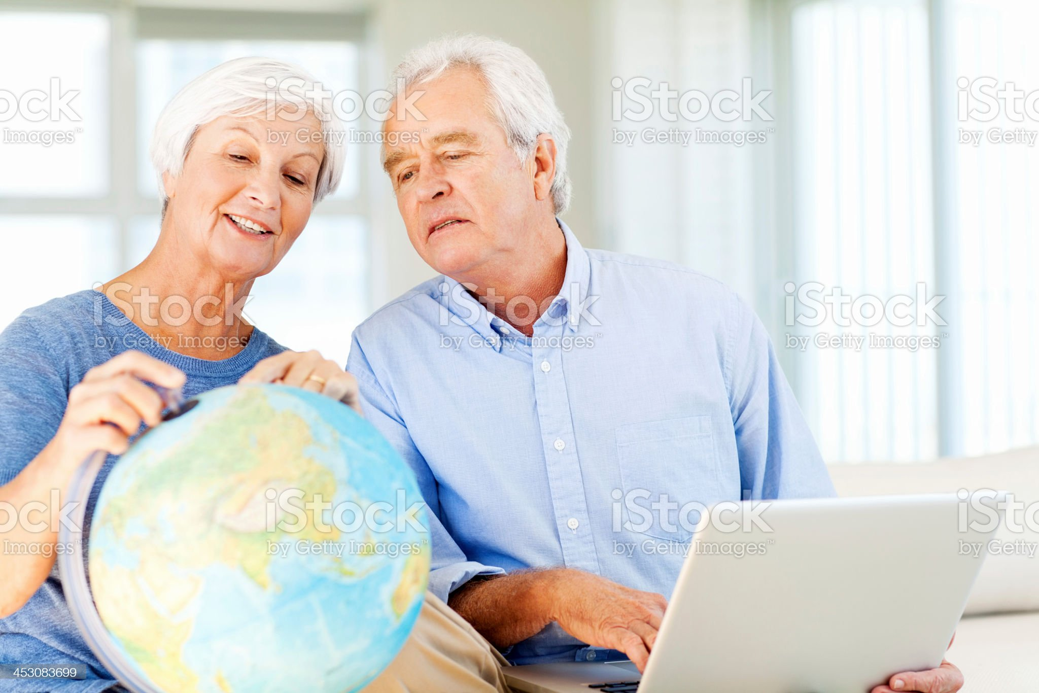 Senior Couple With Laptop And Globe Planning For Vacation royalty-free stock photo