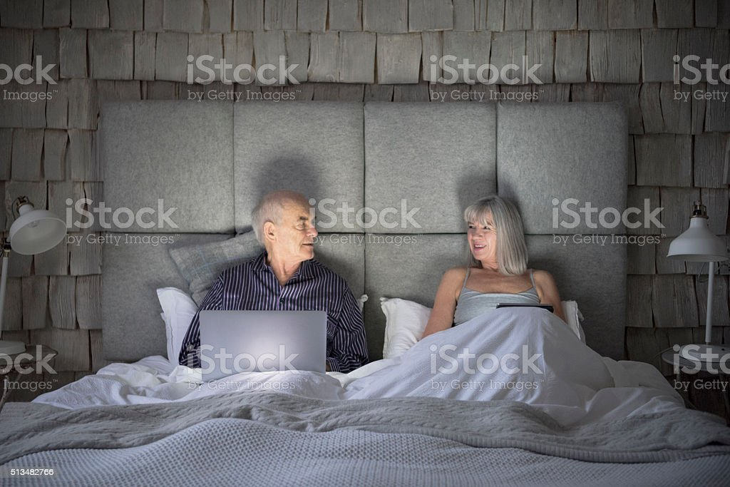 Senior couple with laptop in bed looking at each other stock photo